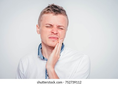 Closeup portrait of young man with tooth ache crown problem about to cry from pain touching outside mouth with hand, isolated white background. Negative emotion facial expression feeling