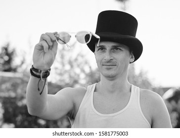 Close-up portrait of young man, wearing white top and black classic hat, holding sunglasses, smiling. Black and white picture of creative man on abandoned construction site area. Art-house.