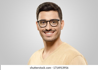 Close-up portrait of young man wearing beige t-shirt and trendy glasses, looking at camera with happy smile, isolated on gray background. Eyewear ads concept
