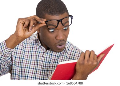 Closeup portrait of young man, with wide opened eyes staring at a book page, shocked, surprised by the twists and turn of story, isolated on white background. Human emotion, facial expression, feeling