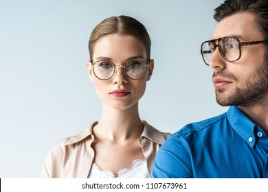 close-up portrait of young man and woman in stylish clothing and eyeglasses isolated on white