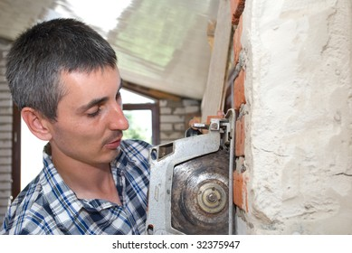 Closeup portrait of a young man working on circular saw
