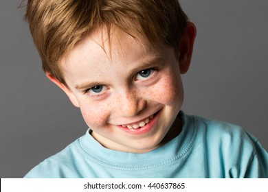 closeup portrait of a young mischievous child with freckles and adorable blue eyes teasing and smiling, grey background studio