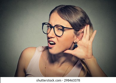 Closeup portrait young nosy woman hand to ear gesture trying carefully intently secretly listen in on juicy gossip conversation news  isolated gray background. Human face expression. Hard to hear