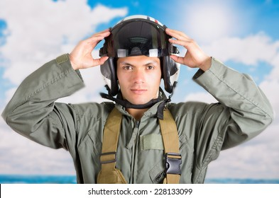 closeup portrait of young pilot holding helmet with a sky background