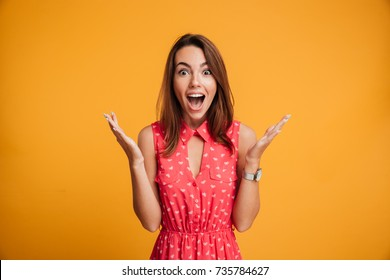 Close-up portrait of young pretty surprised woman with opened mouth standing with open palms, isolated on yellow background