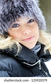 Closeup portrait of young pretty woman in winter coat outdoors