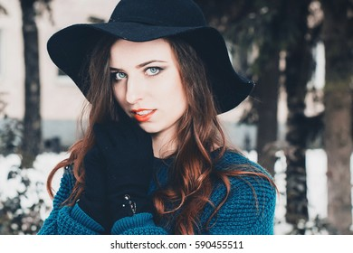 Closeup portrait of a young pretty woman in emerald oversize sweater, gloves and black hat
