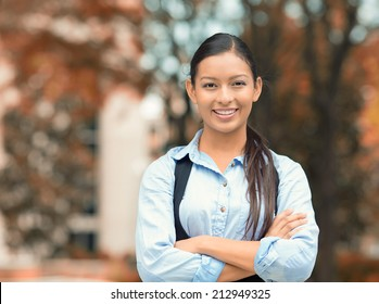 Closeup portrait, young professional, beautiful confident businesswoman in blue shirt smiling isolated outdoor trees background. Positive human emotions, facial expressions, attitude, life perception