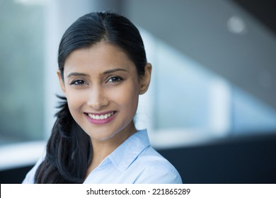 Closeup portrait, young professional, beautiful confident woman in blue shirt, friendly personality, smiling isolated indoors office background. Positive human emotions