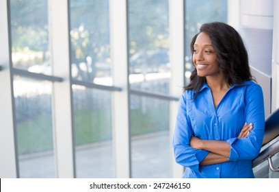 Closeup portrait, young professional, beautiful confident woman in blue shirt, friendly personality, smiling, looking outside glass window, isolated indoors office background. Positive human emotions