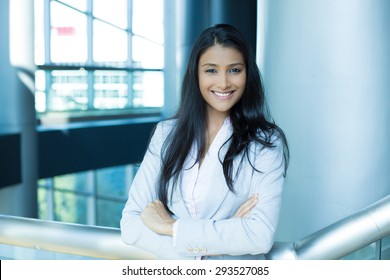 Closeup portrait, young professional, beautiful confident woman in pink shirt gray suit, arms crossed folded, smiling isolated indoors office background. Positive human emotions