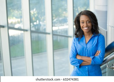 Closeup portrait, young professional, beautiful confident woman in blue shirt, friendly personality, smiling, standing in front ot glass window, isolated indoors office background. Positive emotions