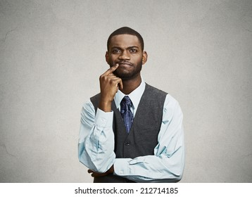 Closeup portrait young, puzzled business man thinking, deciding deeply something, finger on lips looking confused, unsure isolated grey wall background with texture. Emotion facial expression feeling