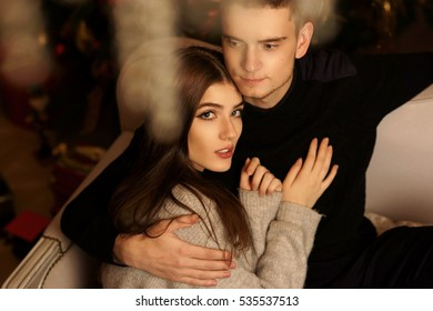 Closeup portrait of young romantic caucasian couple sitting and hugging in christmas decorated interior. Cute lovers staying at home and enjoying tome together
