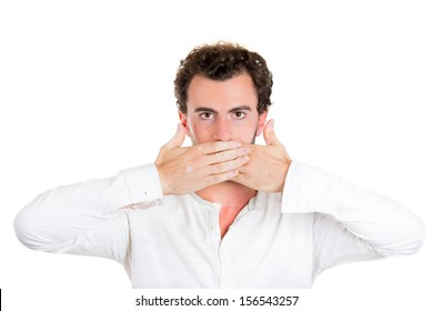 Closeup portrait of a young serious handsome man covering his mouth. Speak no evil concept, isolated on white background. Media news cover up and misrepresentation. Politics, corporate relation.