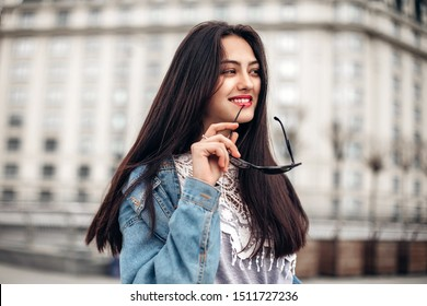 close-up portrait of a young sexy brunette hipster girl. dressed in a stylish large denim jacket holds sunglasses in hand