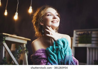 close-up portrait of a young sexy slender beautiful girl in knit from yarn knitted sweater with bare shoulders and graceful arms and collarbones smiling and posing in the studio  a background  lights