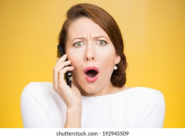 Closeup portrait young shocked business woman, corporate employee talking on cell phone, having unpleasant, bad conversation, isolated yellow background. Negative emotion, facial expressions, reaction