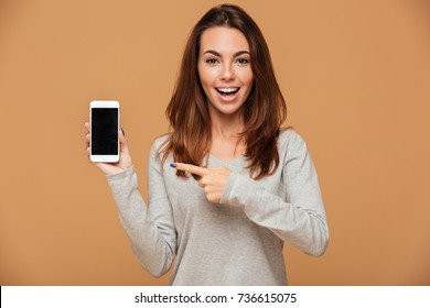 Close-up portrait of young smiling brunette woman pointing with finger on blank mobile screen, looking at camera, isolated on beige background