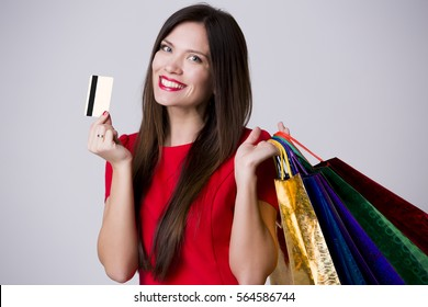 Close-up portrait of young smiling female holding credit card isolated on white background with shoping bags