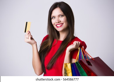 Close-up portrait of young smiling female holding credit card isolated on white background with shoping bags.