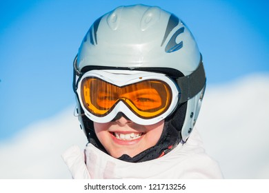 Closeup portrait of young smiling girl in helmet and ski googles at winter outdoor in the Zillertal Arena, Austria