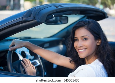 Closeup portrait young smiling, happy, attractive woman smiling from behind in her brand new sports car drop top, hand on steering wheel, isolated outdoors background