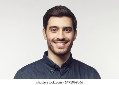 Close-up portrait of young smiling man in denim shirt isolated on gray background