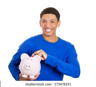 Closeup portrait of young smiling school student, worker man holding piggy bank, isolated on white background. Smart currency financial investment wealth decisions. Budget management and savings