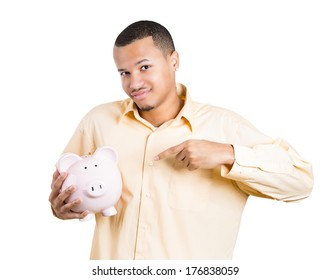 Closeup portrait of young smiling school student, worker man holding pointing to piggy bank, isolated white background. Smart currency financial investment wealth decisions. Budget management, savings