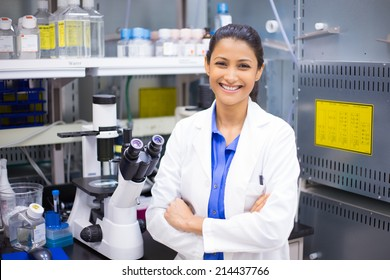 Closeup portrait, young smiling scientist in white lab coat standing by microscope. Isolated lab background. Research and development.
