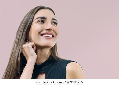 Closeup portrait of young smiling woman, caucasian female's face on beige pink pastel background.
