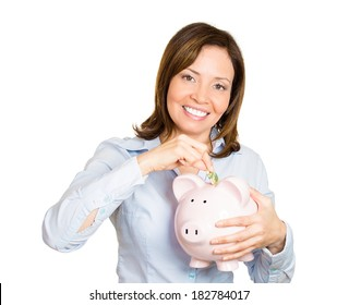Closeup portrait of young smiling worker woman holding, depositing money into piggy bank, isolated white background. Smart currency financial investment wealth decisions. Budget management and savings