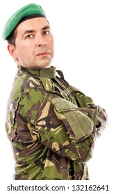 Closeup portrait of a young soldier with arms folded against white background