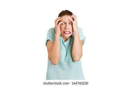 Closeup portrait of young stressed, annoyed, mad woman with hands on head, eyes crossed, going insane, isolated on white background, copy space on both sides. Negative human emotion, facial expression