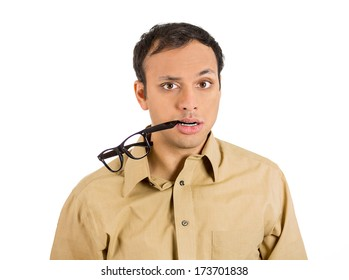 Closeup portrait young stressed man, anxious student, upset worker, nervous teacher, glasses in mouth, looking completely lost, confused, isolated on white background. Negative emotions, expressions