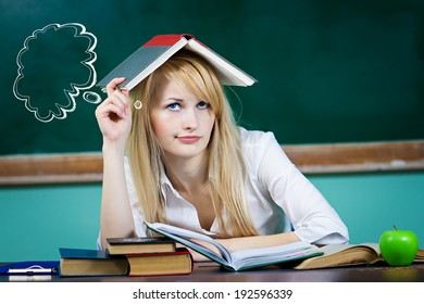 Closeup portrait young student woman, sitting at desk in classroom, looking upwards, confused, thinking, tired, upset, book on head isolated green chalkboard background with bubbles. Human emotions