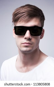 Close-up portrait of a young stylish beautiful  man with black glasses on a grey background
