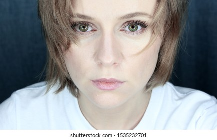 Closeup portrait of a young stylish woman with green eyes and blond hair on a dark blue background.Very serious, attentive look. Ring light is reflected in the eyes.
