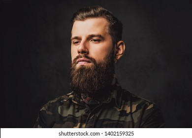 Closeup portrait of a young tattooed man with beard and hairstyle. Studio photo against a dark wall
