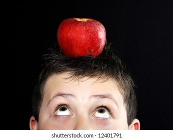 closeup portrait of a young teen boy with an apple on his head