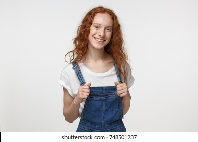 Closeup portrait of young teenage girl with red loose hair pictured isolated on white background pulling forward straps of her denim jumpsuit, smiling happily at camera feeling joy and satisfaction
