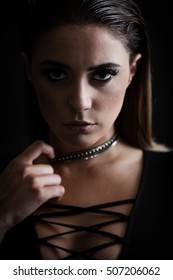 Closeup portrait of a young trendy agressive woman in bodysuit posing near black wall