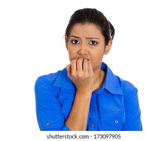 Closeup portrait of young unhappy woman biting her nails and looking at you with a craving for something or anxious worried isolated on white background. Negative emotion facial expression feelings