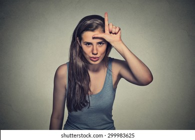 Closeup portrait young unhappy woman giving loser sign on forehead, looking at you, disgust on face isolated on gray wall background. Negative human emotion facial expression
