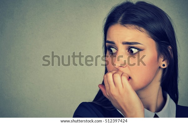 Closeup portrait young unsure hesitant nervous woman biting her fingernails craving for something or anxious isolated on gray wall background. Negative human emotions facial expression feeling
