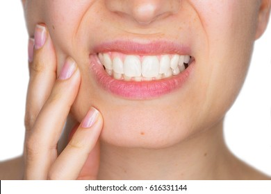 Closeup portrait of young woman achy girl suffering from terrible tooth pain, touching pressing her cheek. Dental care and toothache.