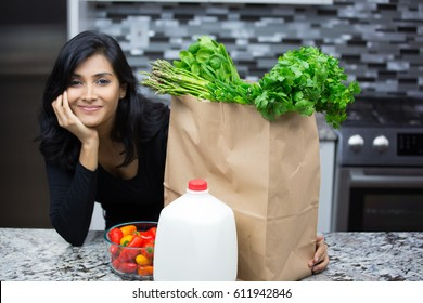 Closeup portrait, young woman with bag full of groceries, healthy nutritious balanced diet, isolated indoors home background. Locally sourced food