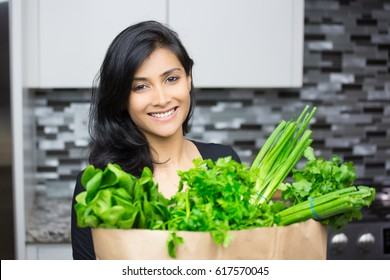 Closeup portrait, young woman with bag full of green groceries, healthy nutritious balanced diet, isolated indoors home background. Locally sourced food